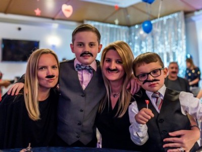 Image of two mothers and their sons wearing fake mustaches