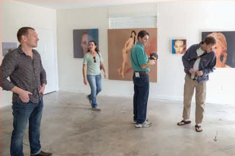Image of four people looking at paintings in an art gallery
